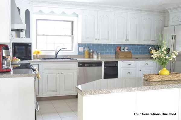 White kitchen cabinets, gray speckled countertop, blue glass tile backsplash, red blender, red kitchenaid mixer, wood bread box, glass canisters