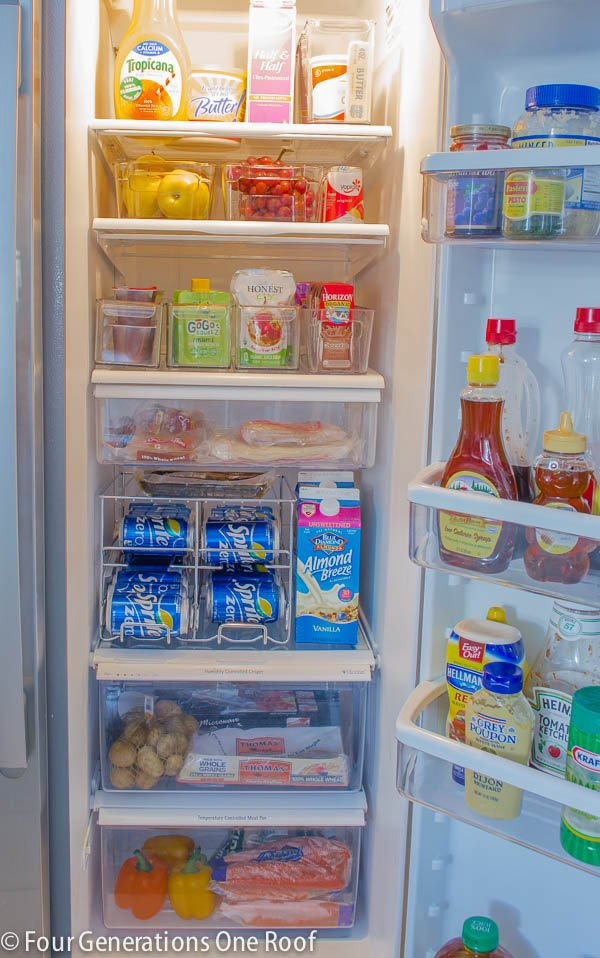 Refrigerator full of plastic bins and containers to organize food