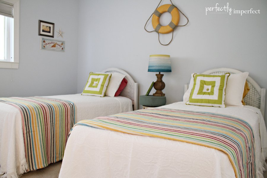 Beach style bedroom is filled with a white upholstered bed dressed in green and blue velvet pillows placed next to a small mirrored nightstand and a cream lamp placed in .