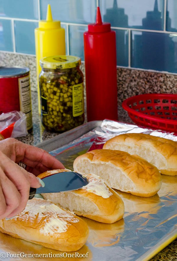 Kings Hawaiian hot dog rolls with butter spread on top, cookie sheet lined with tin foil, relish, ketchup
