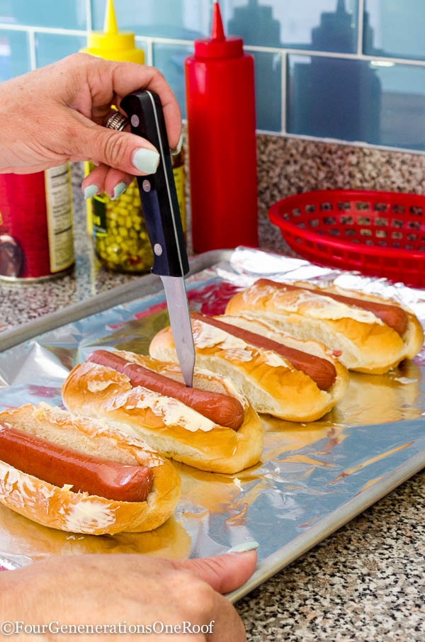 Kings Hawaiian hot dog rolls with butter spread on top, hot dog, cookie sheet lined with tin foil, relish, ketchup, knife