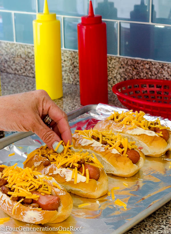 Kings Hawaiian hot dog rolls, hot dog, baked beans, cheddar cheese with butter spread on top, cookie sheet lined with tin foil, relish, ketchup
