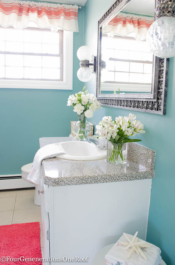 small blue paint bathroom with iron mirror, glass metallic light fixture, white and coral valance
