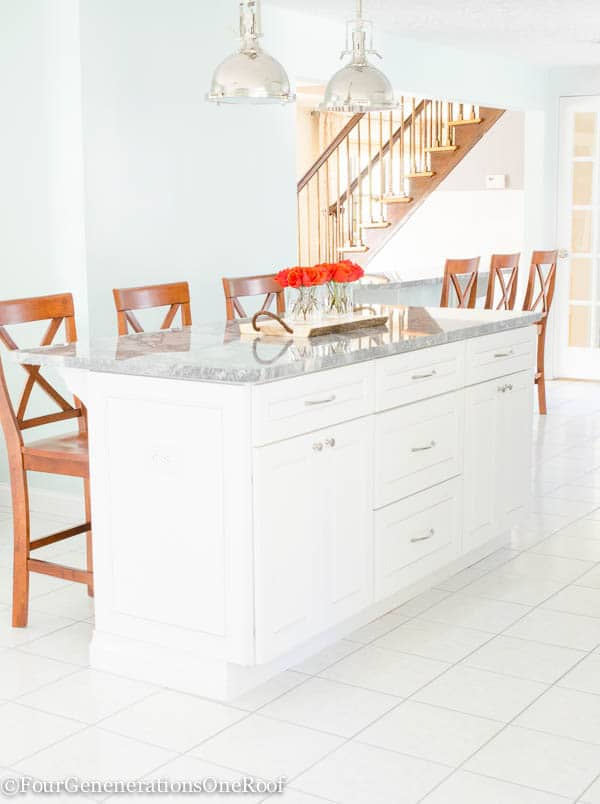 white kitchen island, brown x back bar stools, nickel dome light pendants, white tile floor, rainwash blue walls