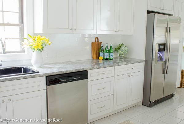 Our kitchen renovation reveal {before & after} This is an amazing before and after transformation. Gorgeous white cabinets, harmon pendants, quartzite super white counters and backsplash.