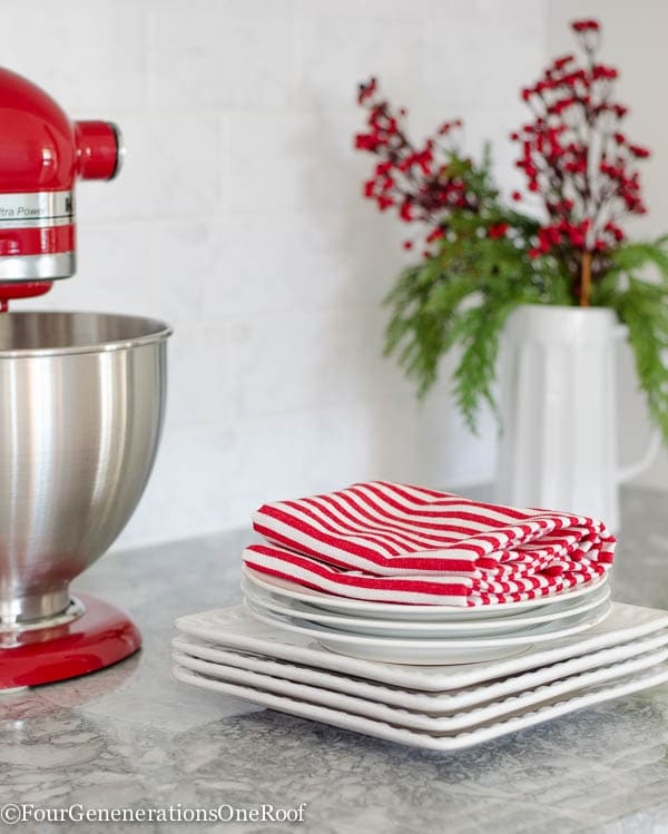 Traditional Christmas Home Tour 2015 Our Christmas Kitchen 2015: boxwood wreaths, red velvet ribbon, boxwood Christmas tree, red striped hand towel, greens and holly berry.