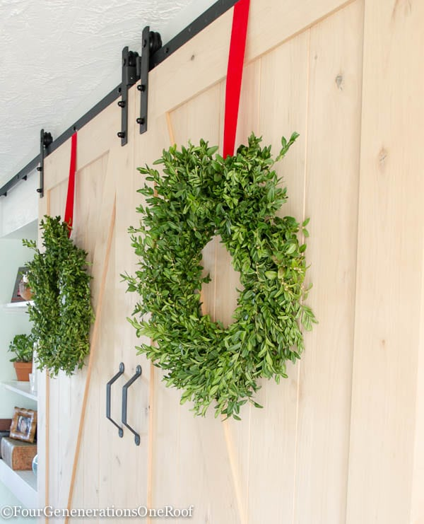 Our Christmas Kitchen 2015: boxwood wreaths, red velvet ribbon, boxwood Christmas tree, red striped hand towel, greens and holly berry.