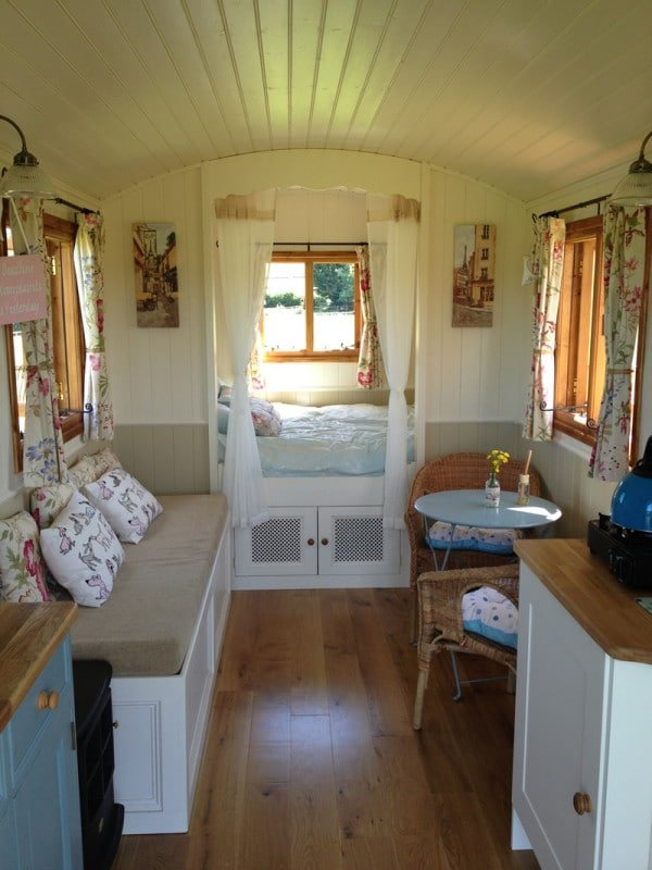 resorted old camper with drapes, hardwood floor and decorative throw pillows, built in bed
