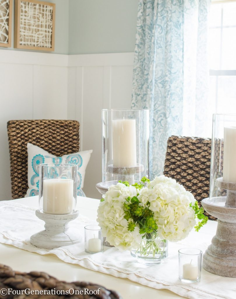 Seasalt paint color, seagrass chairs, white farmhouse table, tan rope rug, stone candle pillars, blue curtains, white board and batten wall