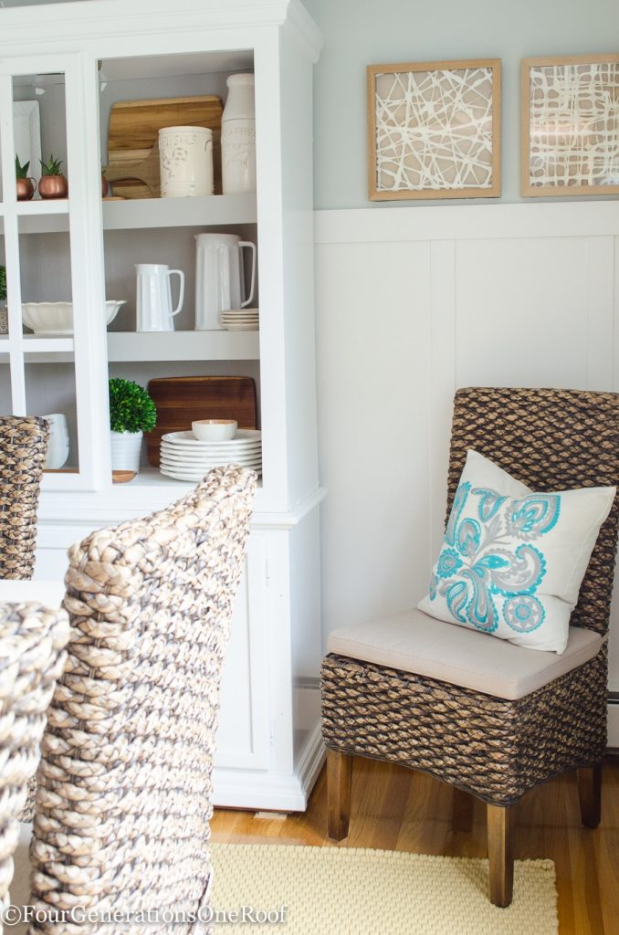 Modern Coastal Farmhouse Dining room with Seagrass chairs Seasalt paint color, seagrass chairs, white farmhouse table, tan rope rug, stone candle pillars, blue curtains, white board and batten wall