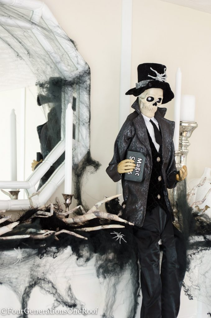 halloween white mantel with black skeleton, white mirror, black spider webs