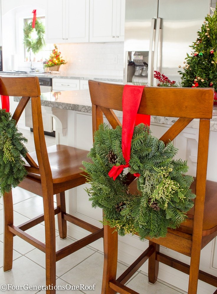 Christmas Kitchen 2016 | Featuring hanging wreaths on the barn doors, hanging wreaths on the stools and windows along with a mini boxwood Christmas tree as a centerpiece on the island | Four Generations One Roof