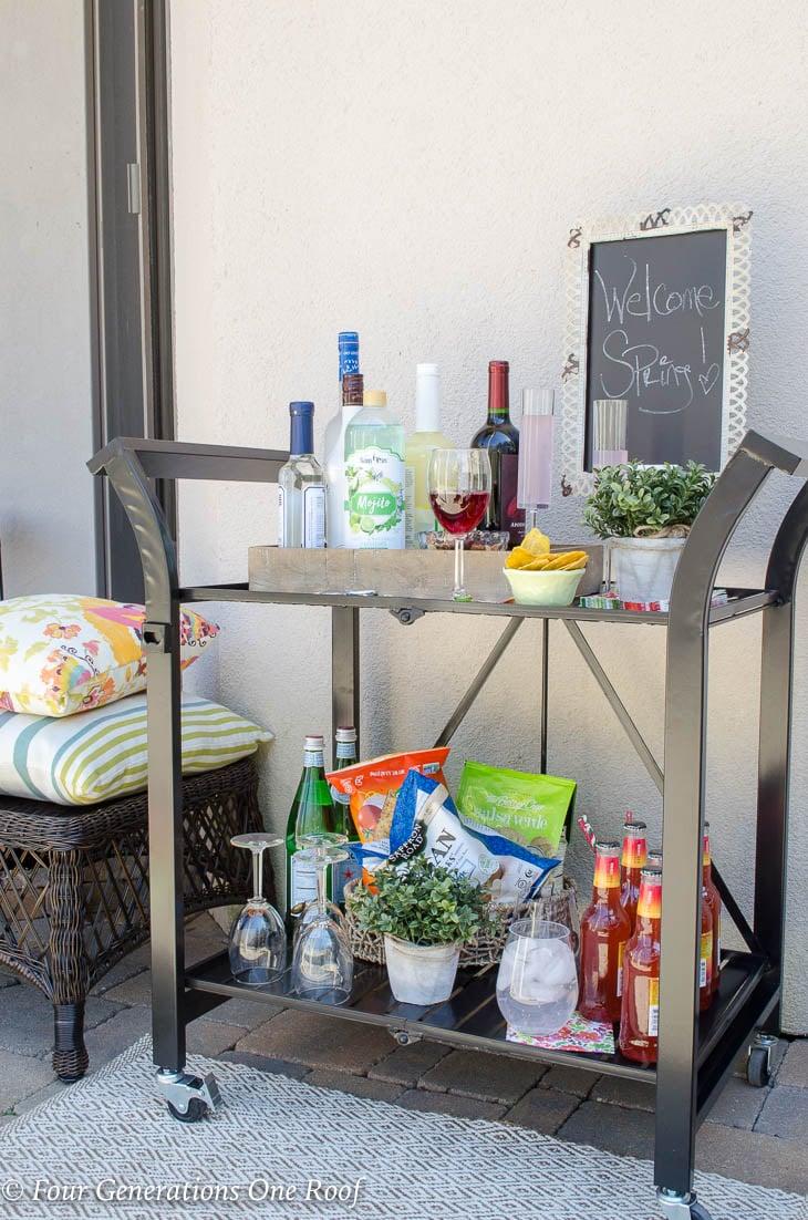 15 minute black metal bar cart setup | wooden tray filled with liquor and mixers | champaign glasses | chalk board sign #barcart #liquor #entertaining #blackbarcart #metalbarcart #patiodesign #outdoorentertaining #entertainingideas