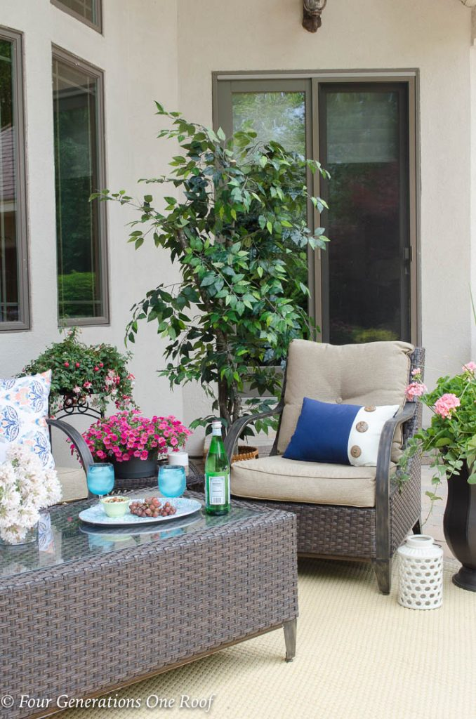 brown wicker furniture on patio with plants and trees