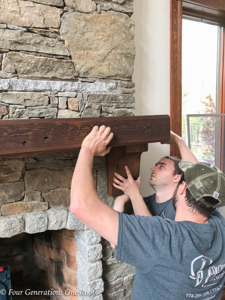 woodworkers hanging a dark stained wood rustic mantel on stone fireplace