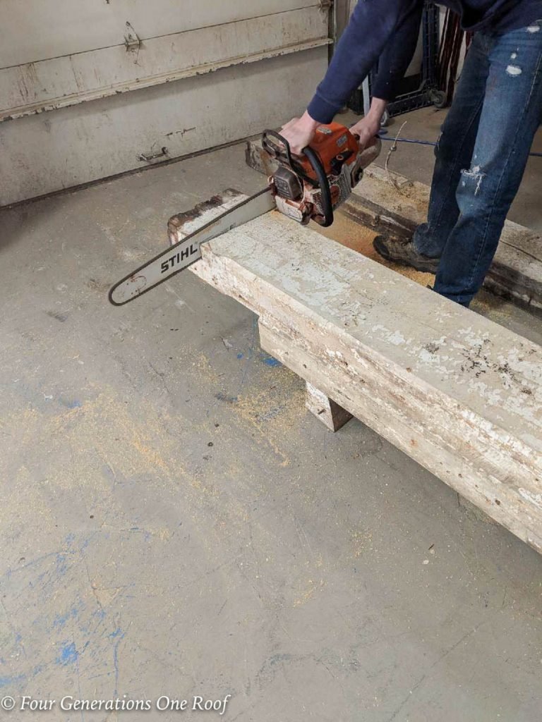 white painted pine beam mantel being cut to size with a chainsaw