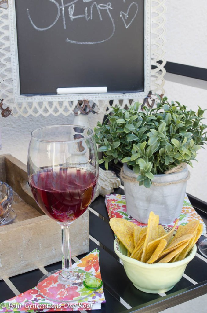 15 minute black metal bar cart setup | plate of banana chips | glass of red wine | wooden tray filled with liquor bottles and mixers