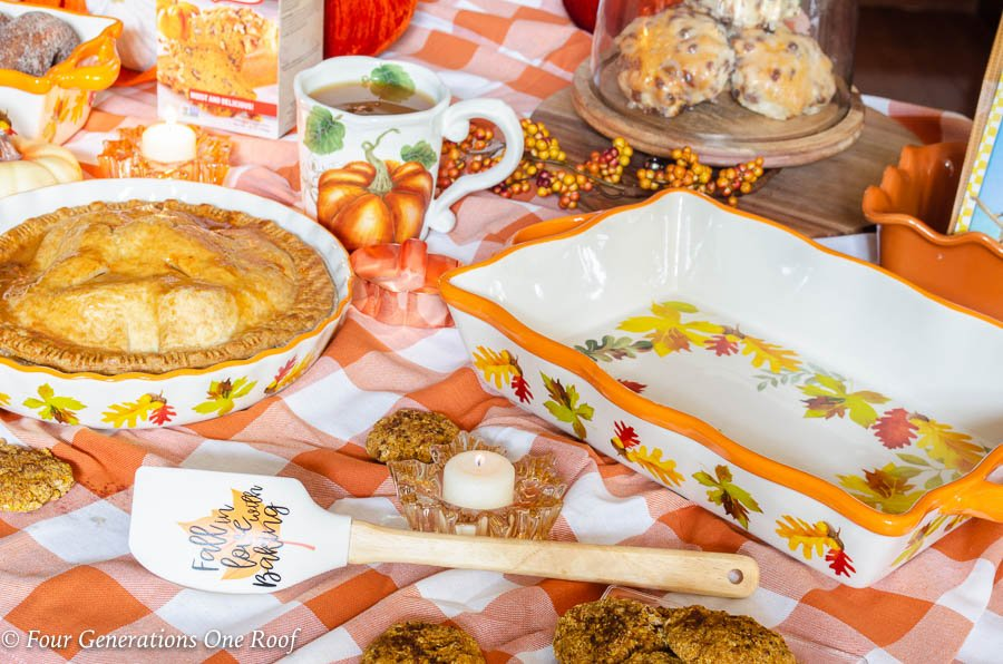 Kitchen Island Fall Snack Station with orange plaid tablecloth, Harvest dog sign, Harvest bakeware, pumpkins, apple pie, apple cider, donuts, pumpkin cookies and baked goods