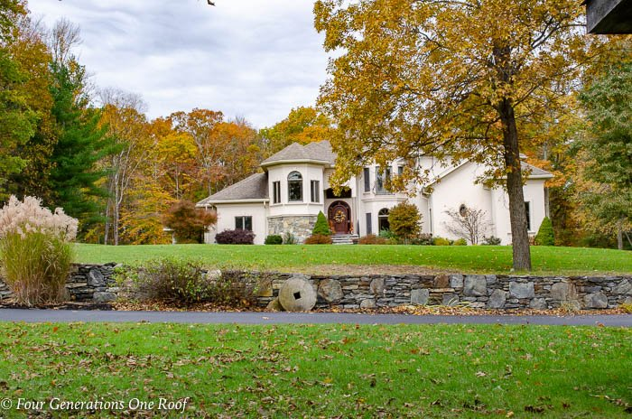 European Mediterranean Home with hip roof and cherry stained front door fall new england leaves
