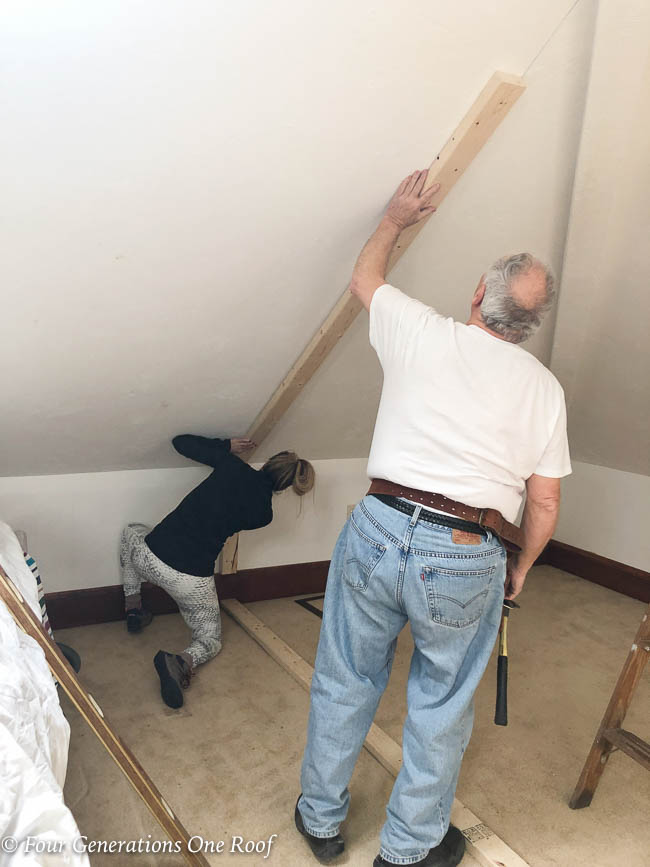 Jessica Bruno nailing 2x4 to slanted ceiling