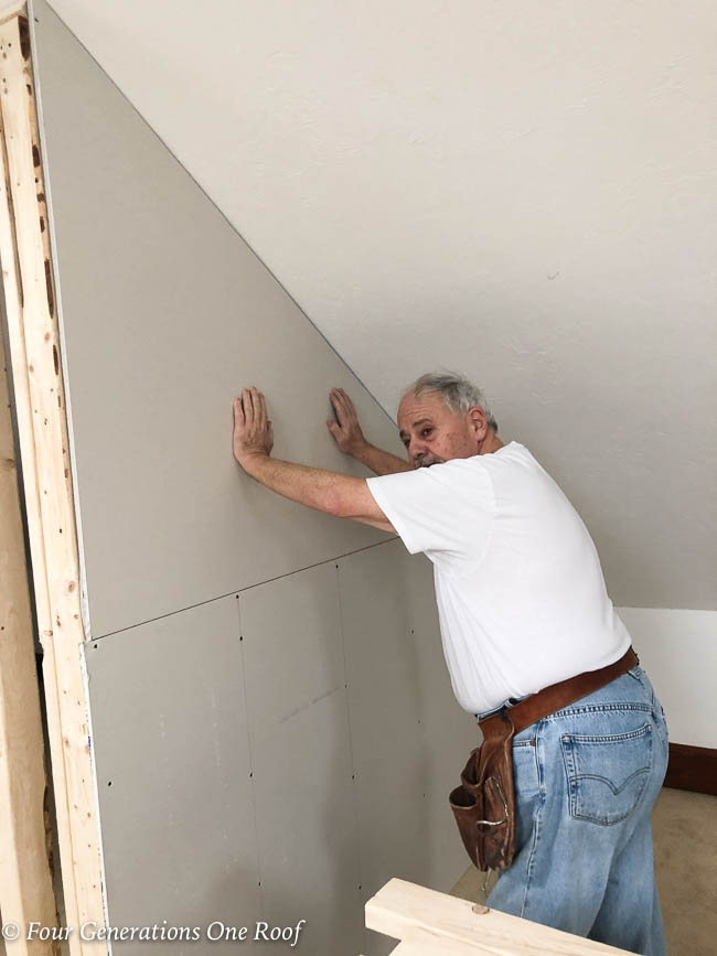 Jessica Bruno's dad holding up the drywall on the closet wall