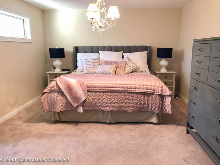 Master bedroom with pink bedding, tan walls and blue lamp shades
