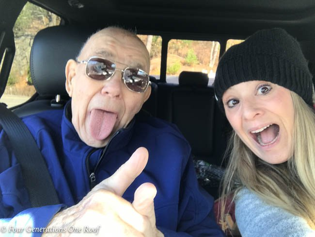grandfather and granddaughter in car thumbs up