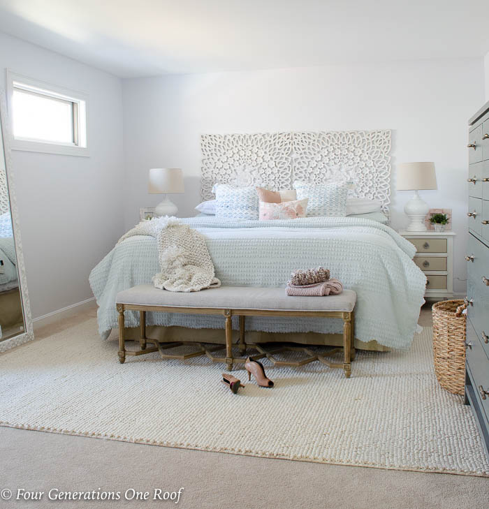 white scroll headboard, mint green bedding, mint green comforter, white night table, white lamp, blue tassel throw pillow, green plant, french country bench, cable knit beige throw blanket, beige popcorn rug over carpt