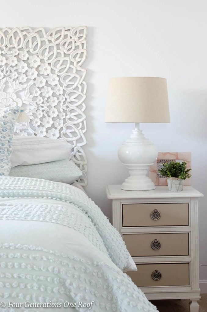 white scroll headboard, mint green bedding, mint green comforter, white night table, white lamp, blue tassel throw pillow, green plant