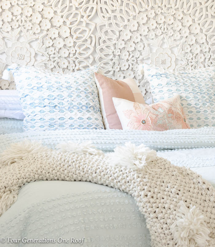 fluffy white comforter, white scroll headboard, mint green bedding, mint green comforter, white night table, white lamp, blue tassel throw pillow, green plant, french country bench, cable knit beige throw blanket
