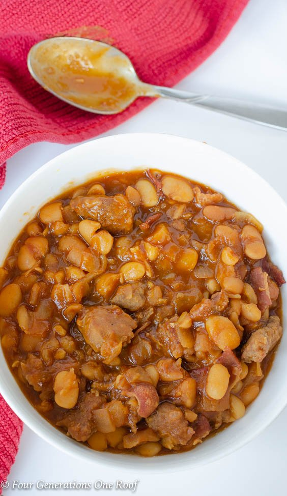 crockpot baked beans with sausage, white bowl, red napkin