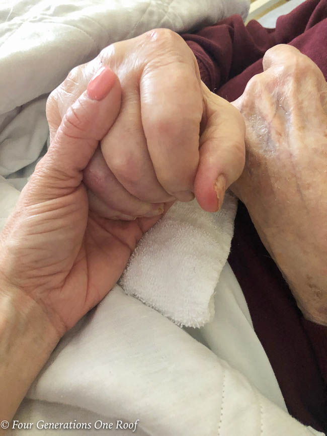 grandfather and granddaughter holding hands in hospital bed