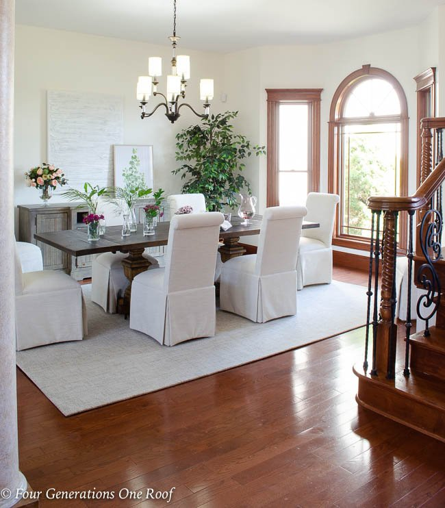 Arhaus dining table, slipcovered parson chairs, updated lighting with Hinkley Modern Traditional Chandelier, greenery, Dash and Albert off white wool rug