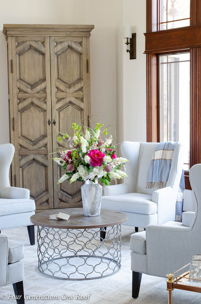gray wingback chairs, ESCHER NATURAL dash and albert rug, round coffee table, large rustic storage cabinet, Sussex wall sconce by Hinkley, vase with flowers,