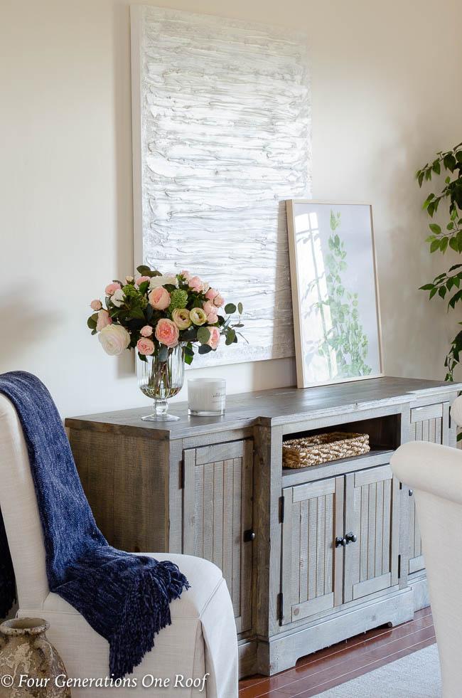 dining room buffet, peonies in vase, white slipcovered parson chair, leaf greenery artwork, modern white textured artwork