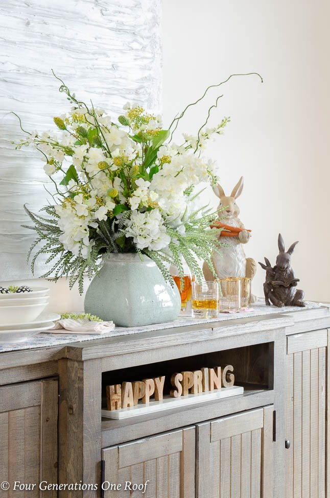 Wood farmhouse buffet table, wood Easter bunnies, flowers, white modern artwork, white Tuscan dishes, Happy Spring Sign, White slipcovered parson dining chairs