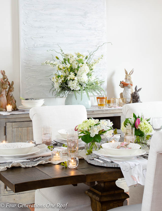Table setting for Spring and Easter, white tuscan dishes, Easter linens, hydrangeas, wood scroll chargers, gold glassware, wooden Easter bunnies, ruffled beige table runner
