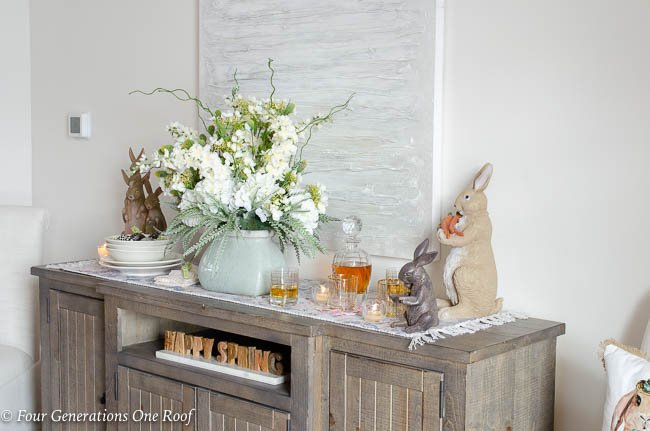 wood dining room buffet table, flowers pastel vase, Happy Spring Sign, glass decanter, modern artwork, gold glassware, Easter bunnies, ruffled beige table runner