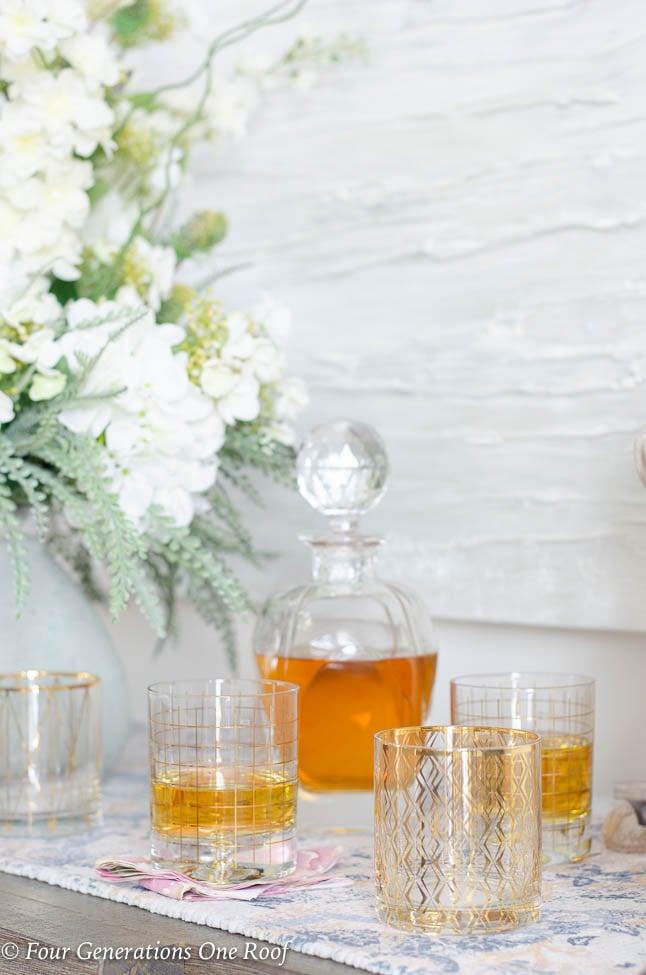 Flowerers, wood buffet table, decanter with liquor, gold rimmed cocktail glasses, pastel table runner, white modern artwork