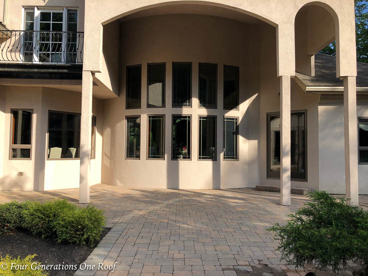 european stucco house patio with pavers and columns and large windows
