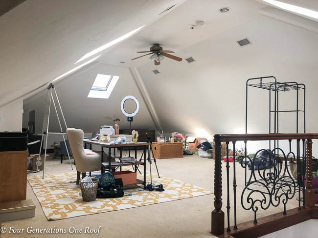 attic loft open space with skylights desk, yellow rug, toys, sectional
