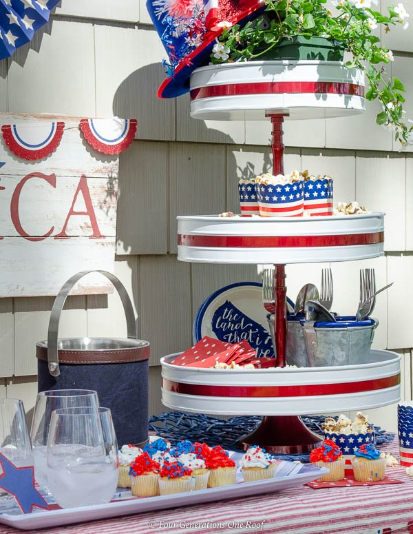 Classy Patriotic Decor Ideas on our Patio patriotic beverage station with patriotic bunting, patriotic banners, white and red 3 tier tray with popcorn, striped platter, red striped tablecloth, American Sign, patriotic fans