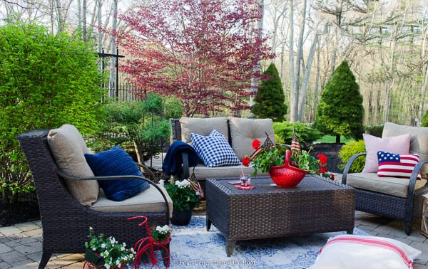 brown rattan outdoor furniture, american flag, red geraniums, blue outdoor rug, red and blue outdoor pillows, red planter, red tricycle planter, japanese maple tree, paver patio