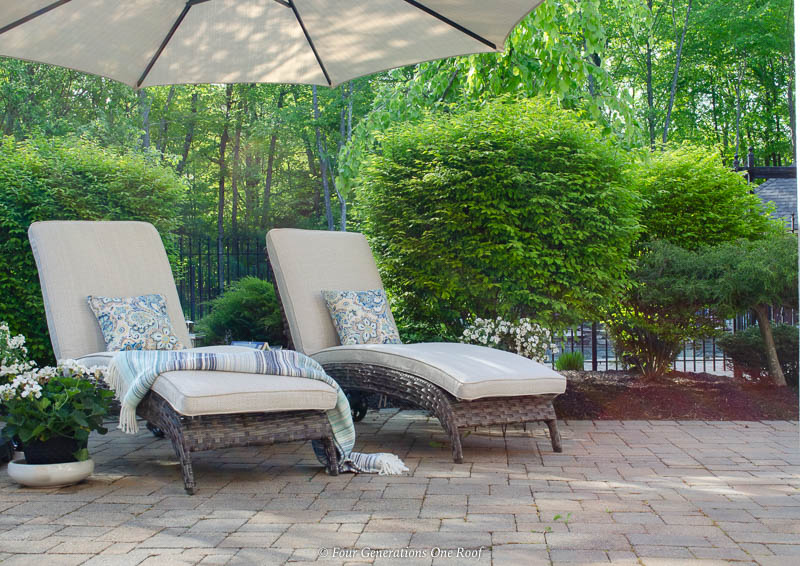 indoor outdoor living space with greenery, sand color umbrella, brown gray rattan outdoor chaise lounge chairs, pool house, blue striped throw blanket, white plants, green shrubs,paver patio