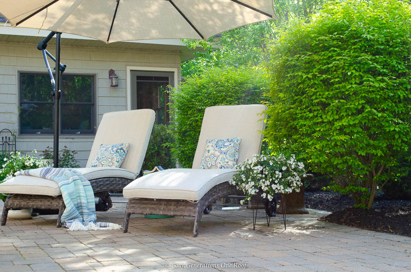 indoor outdoor living space with greenery. sand color umbrella, brown gray rattan outdoor chaise lounge chairs, pool house, blue striped throw blanket, white plants, green shrubs,paver patio