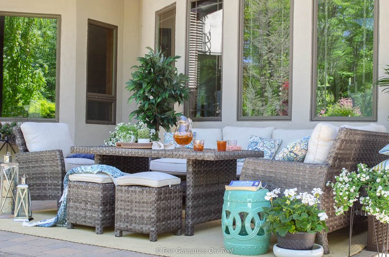 indoor outdoor living space surrounded by nature, outdoor rattan sectional with dining table, chair, ottomans for seating, flowers and trees