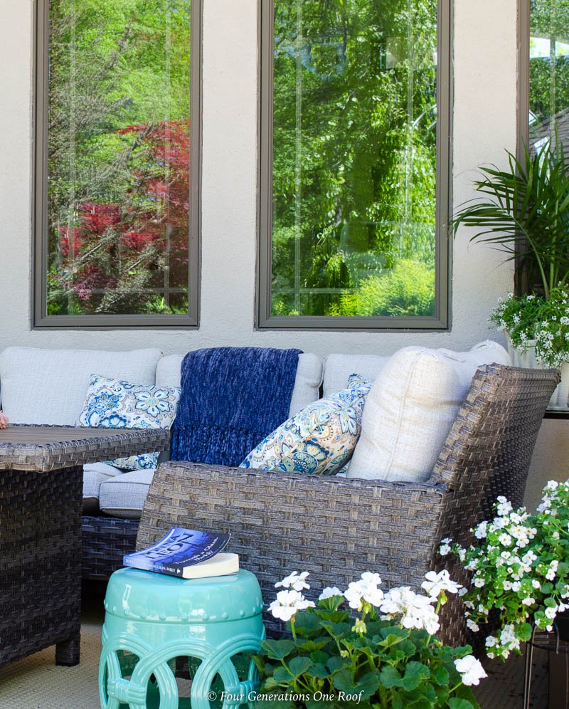 indoor outdoor living space, silver lanterns, tan outdoor rug, brown rattan outdoor chair and sectional with white cushions, blue throw blanket , aqua and blue throw pillows, aqua side table,