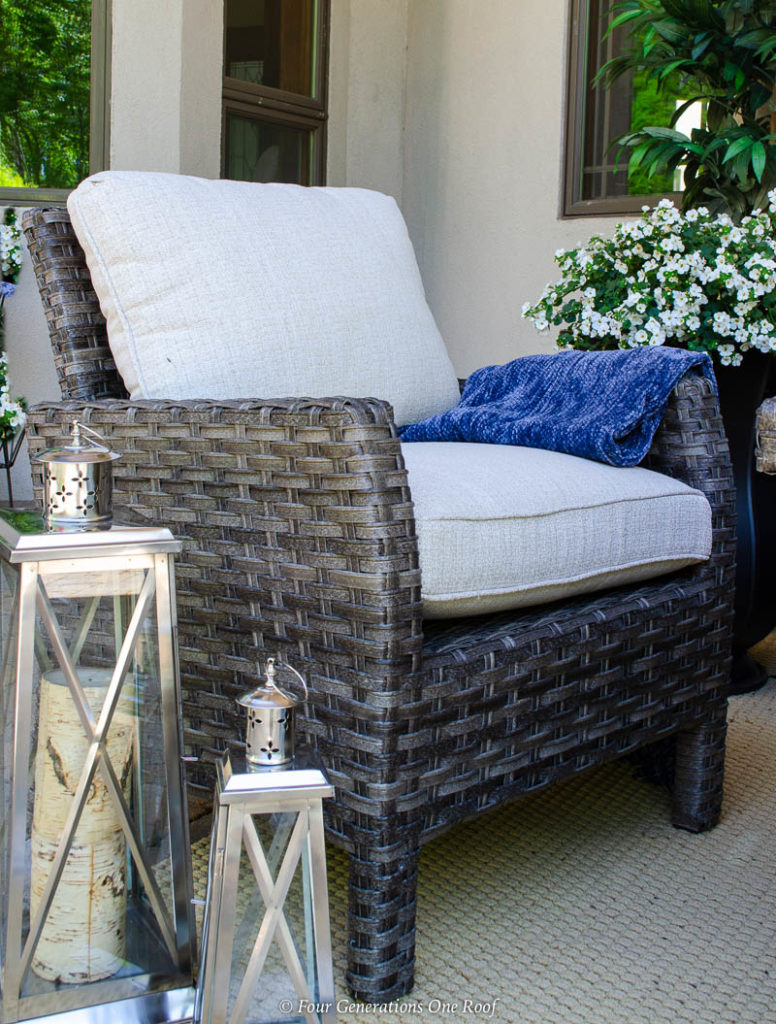 indoor outdoor living space, silver lanterns, tan outdoor rug, brown rattan outdoor chair with white cushions, blue throw blanket