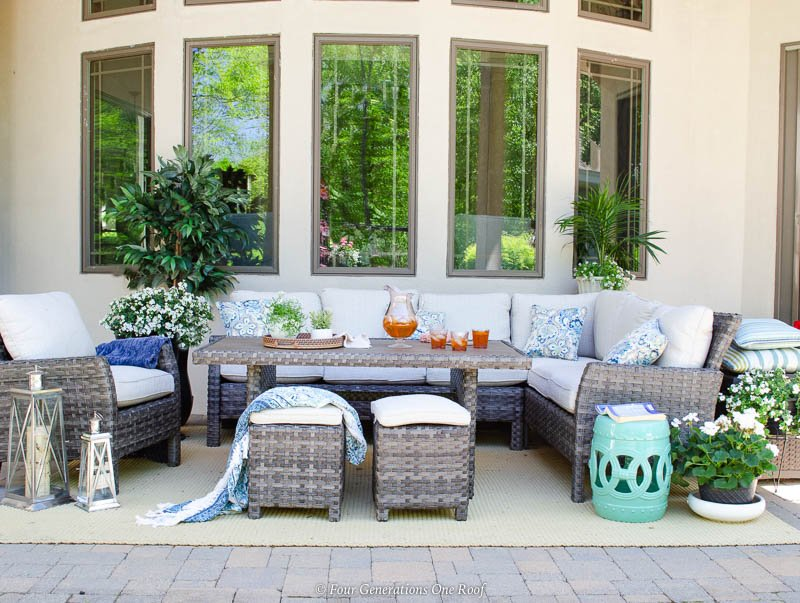 indoor outdoor living space patio, rattan sectional white cushions with dining table and chaise lounge chair with oversized umbrella