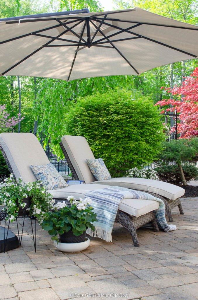 sand color umbrella, brown gray rattan outdoor chaise lounge chairs, pool house, blue striped throw blanket, white plants, green shrubs,paver patio